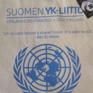"""Vaalea kangaskassi, jossa Suomen YK-liiton logo ja YK:n pääsihteerin sitaatti """"Let us unite behind a shared vision of a safer world"""""""